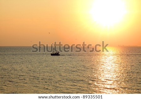 Fishing boat at sunset in Greece - stock photo