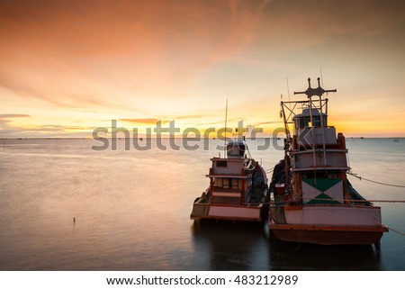 Fishing boat at sunset time with vivid color in the sea ,Thailand