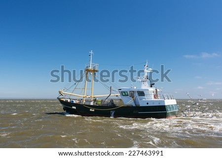 Fishing boat at the Dutch wadden sea - stock photo