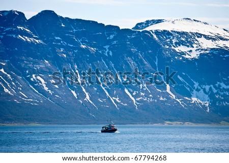 Fishing boat at the rocky coast - stock photo