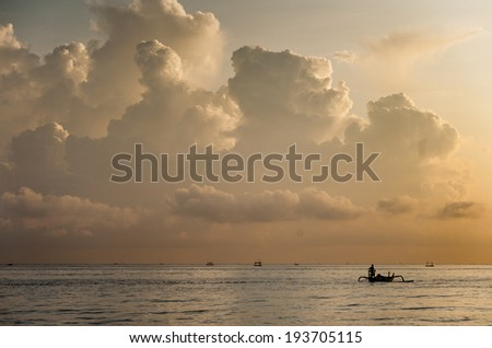 Fishing Boat, Bali, Indonesia. Jemeluk, Amed, Bali. A traditional fishing boat, called a jukung, motors out to sea with the threat of a thunderstorm off in the distance.