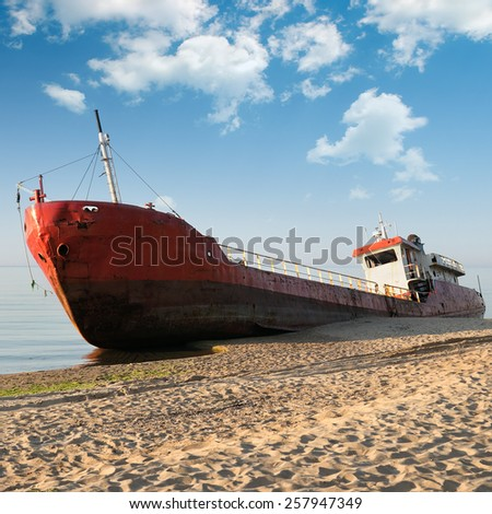 Fishing boat beached and blue sky - stock photo