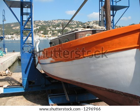 fishing boat being painted in Andratx, Mallorca, Spain - stock photo