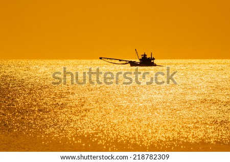 Fishing boat cast anchor on the sea in front of fishing village village, small island, Thailand. - stock photo