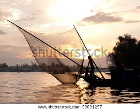 Fishing boat catching fish with fishnet at dusk on the Mekong river. Can Tho, Vietnam - stock photo