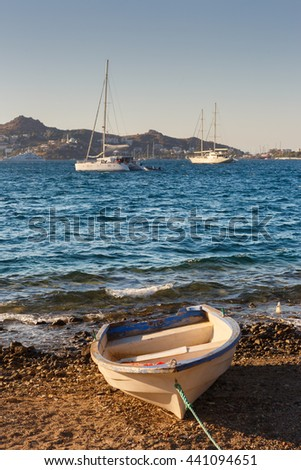 Fishing boat docked to the coast while the luxury yachts sailing in the sea. - stock photo