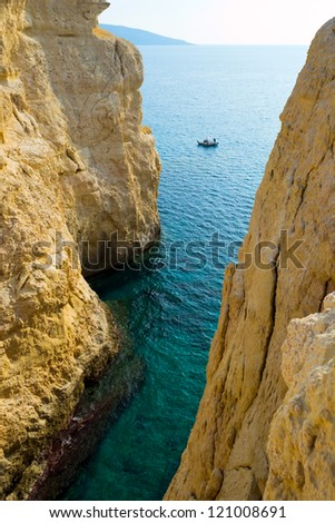 Fishing boat floats in the sea between cliffs