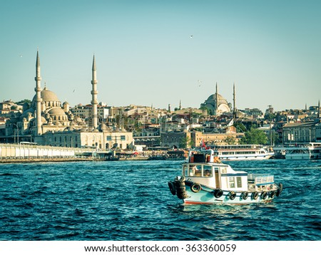 Fishing boat floats on the background of minarets on the Golden Horn in Istanbul, Turkey. View from Galata district. - stock photo