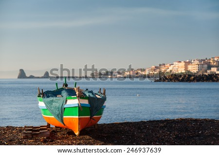 Fishing boat in a beach near the town Acitrezza, Eastsicly, with its houses and typical lava stacks in the distance - stock photo