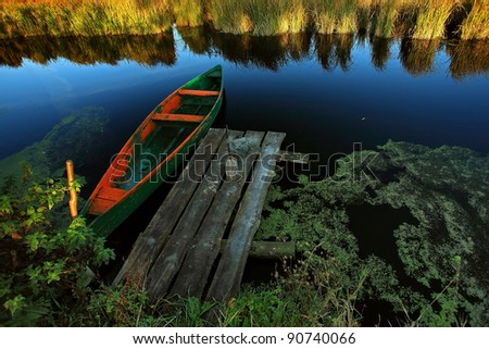 Fishing boat in a quiet backwater near the pier on the lake - stock photo