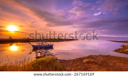 Fishing boat in a river inlet bay during orange sunrise on Lesbos island, Greece - stock photo