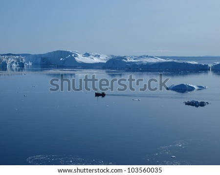 Fishing boat  in front of the icebergs at the mouth of Ilulissat Icefjord. - stock photo