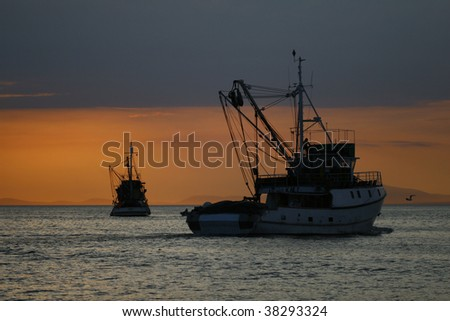fishing boat in sunset - stock photo