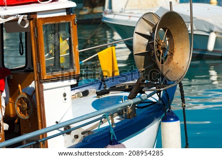 Fishing Boat in the Harbor - Liguria Italy / Blue and white small fishing boat with fishing equipment docked in port - Lerici, La Spezia, Liguria, Italy - stock photo