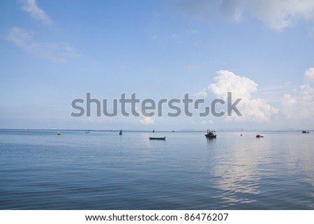 Fishing boat in the sea on blue sky background - stock photo