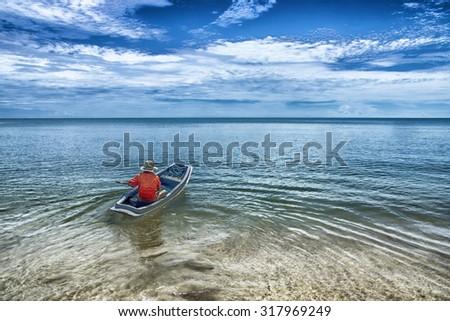 Fishing boat into the sea. - stock photo