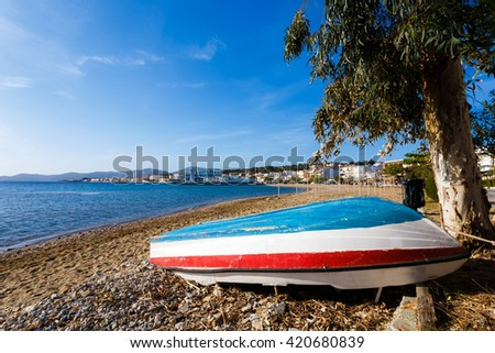 Fishing boat left at shore against a blue sky and clouds in the afternoon in Greece - stock photo