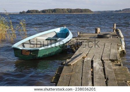 Fishing boat moored by battered wooden jetty, Mazury, Poland - stock photo