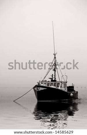 fishing boat moored in the fog