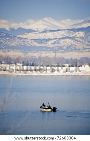 Fishing boat on a lake surrounded by snowy mountain peaks - stock photo