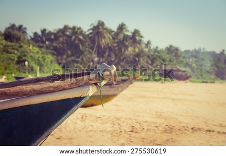 Fishing boat on a tropical beach - stock photo