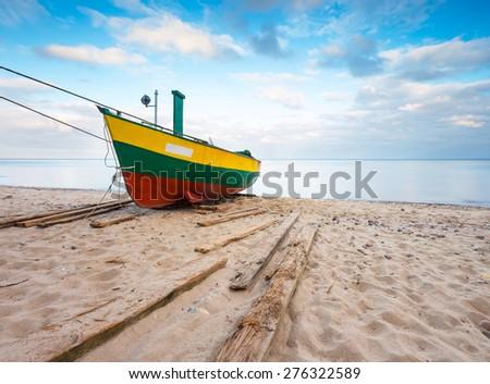 Fishing boat on Baltic sea shore. Beautiful long exposure seascape with fisherman boat. - stock photo