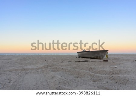 Fishing boat on beach in sunset