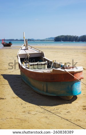 Fishing boat on land in the area of sea tide - stock photo