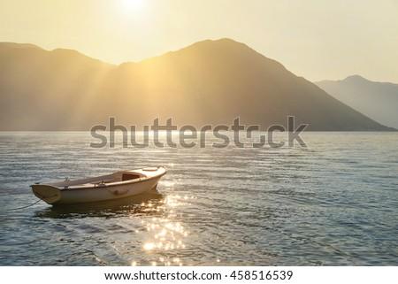 Fishing boat on moorage at sunlight glittering sea surface against sunset Lovcen mountain background with sun rays. Montenegro, Kotor Bay (Boka Kotorska). - stock photo