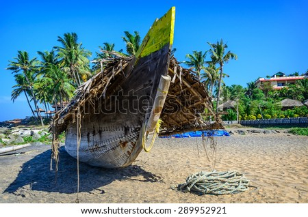 Fishing boat on the beach in the tropical village near the blue ocean in Varkala, Kerala, India - stock photo