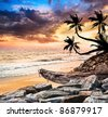 Fishing boat on the beach near the ocean at dramatic sunset sky and palm trees in silhouette nearby - stock photo