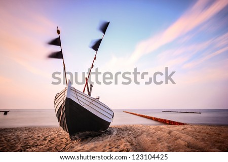 fishing boat on the beach to the baltic sea in the evening light - stock photo