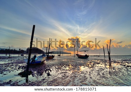 Fishing boat on the beach when sun rising up. Captured on low lighting in the morning when sun rising up. - stock photo