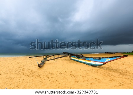 Fishing boat on the beach with dark rain clouds above the ocean - stock photo