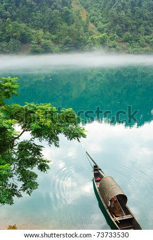 Fishing boat on the foggy river, photo taken in hunan province of China