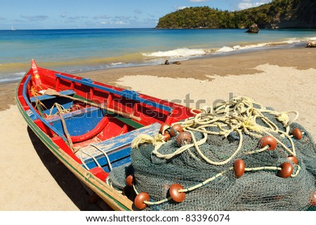 Fishing boat on the light sands of a Caribbean beach with turquoise sea in the background - stock photo