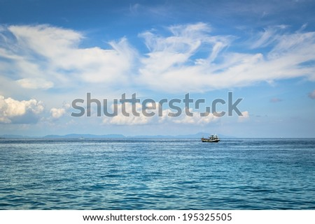 fishing boat on the sea with cloudy blue sky