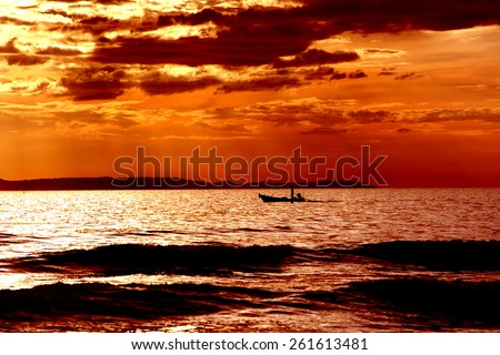 Fishing boat on the water and dramatic clouds at sunrise - stock photo