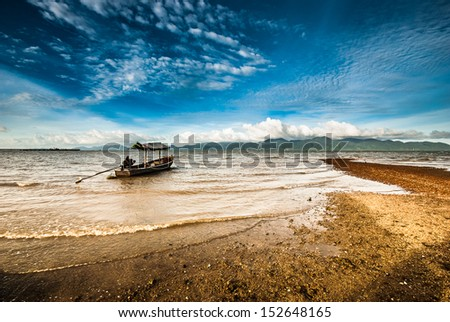 Fishing boat parking opposite the island - stock photo