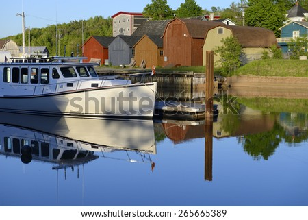 Fishing Boat Reflecting in Smooth Water at Sunset - stock photo