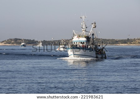 Fishing boat returning to home harbor with lots of seagulls.Croatia - stock photo