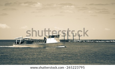Fishing boat returns from fishing with a catch. Toned. - stock photo