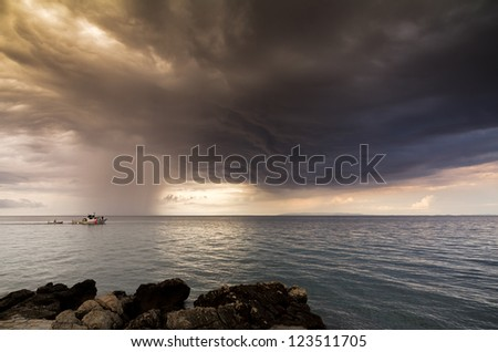 Fishing boat sailing away towards storm clouds on a calm sea - stock photo