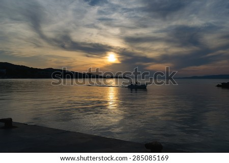 Fishing boat silhouette returning to port against a dramatic sky - stock photo