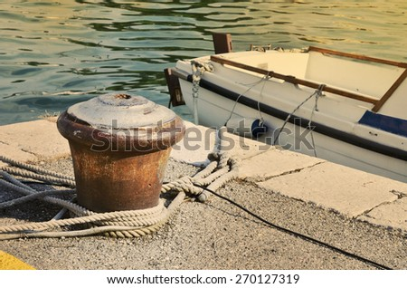 Fishing boat tied to a mooring mast with ropes - stock photo