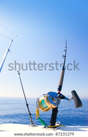 fishing boat trolling with outrigger gear and golden reel rod - stock photo