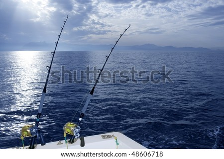Fishing boat trolling with two rods and reels on blue ocean - stock photo