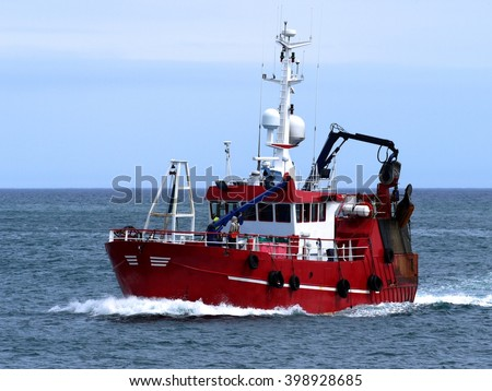 Fishing Boat Underway, langoustine fishing boat arriving harbor to land lagostine lobsters. - stock photo