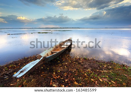 Fishing boat with a beam light of natural in the lake - stock photo