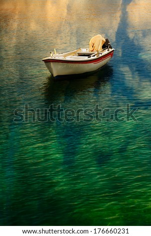 Fishing boat with cloud reflections in water.